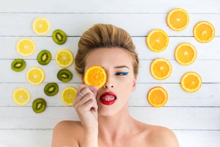 Mulher maquiada com frutas em volta.