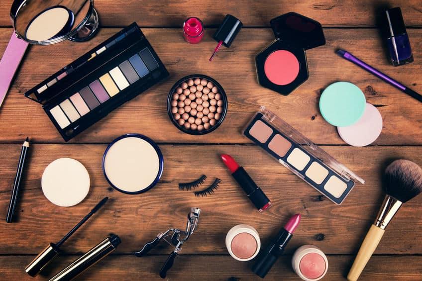 Imagem de diversas maquiagens e acessórios sobre mesa.