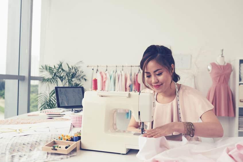 Imagem de mulher costurando em atelier.