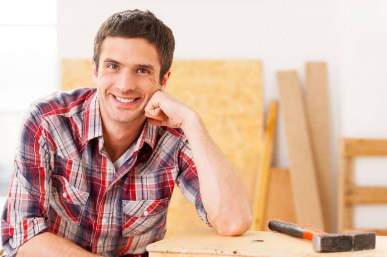 Homem sorri sentado com o braço apoiado em uma mesa de madeira com