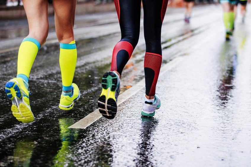 Imagem de duas pessoas correndo com meia de compressão.