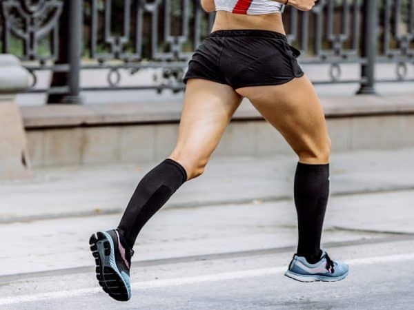 side view of young woman legs in compression socks athlete running a marathon