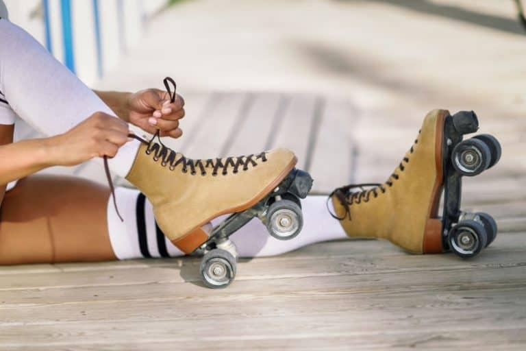 Pessoa vestido patins marrom e usando meião branco.