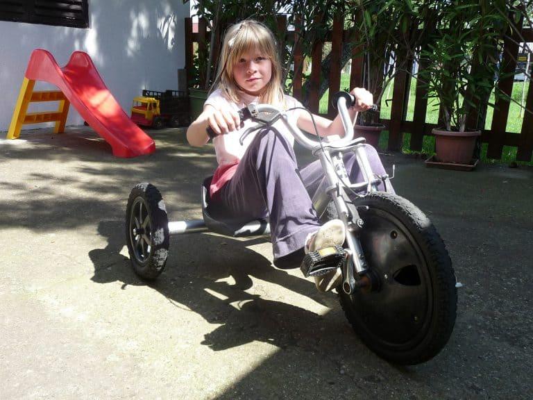 Menina em triciclo elétrico infantil.