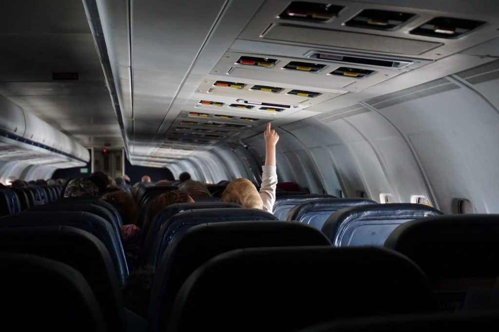 Imagem de menino apertando botão em avião.