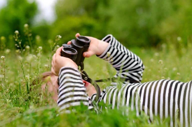 Menino em gramado observando com binóculo.