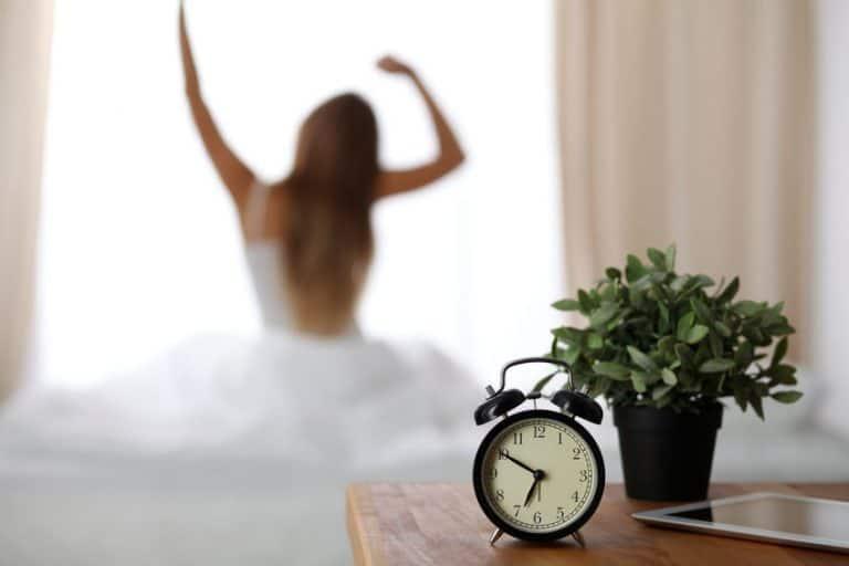 Despertador em criado mudo e pessoa acordando ao fundo.