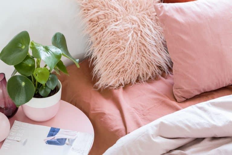 Imagem de cama e criado mudo em tons de rosa.