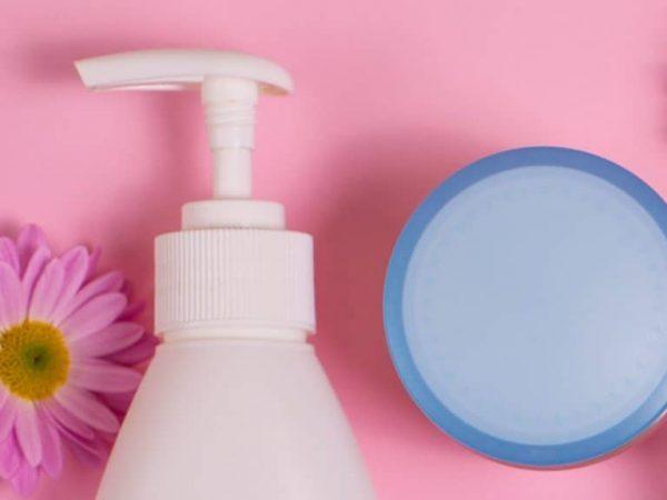 Num fundo rosa, frasco de água micelar ao lado de um pote e flores