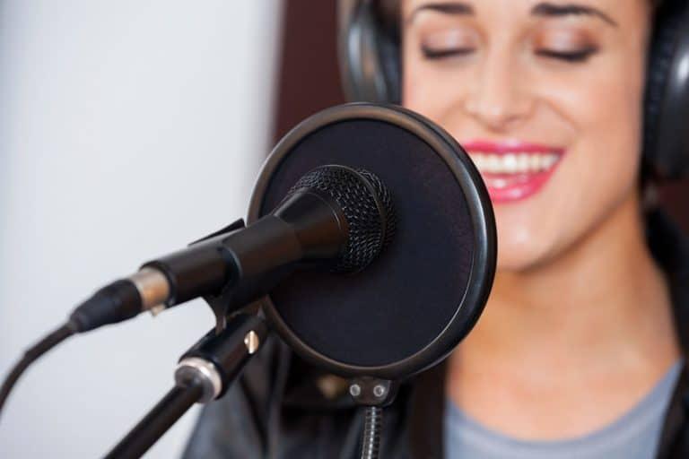 Mulher cantando com microfone condensador.