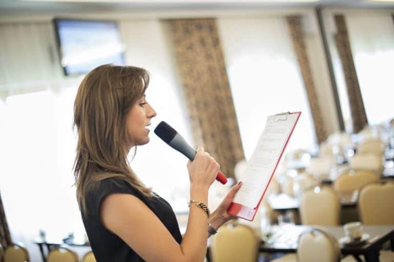 Imagem de mulher falando com microfone sem fio.