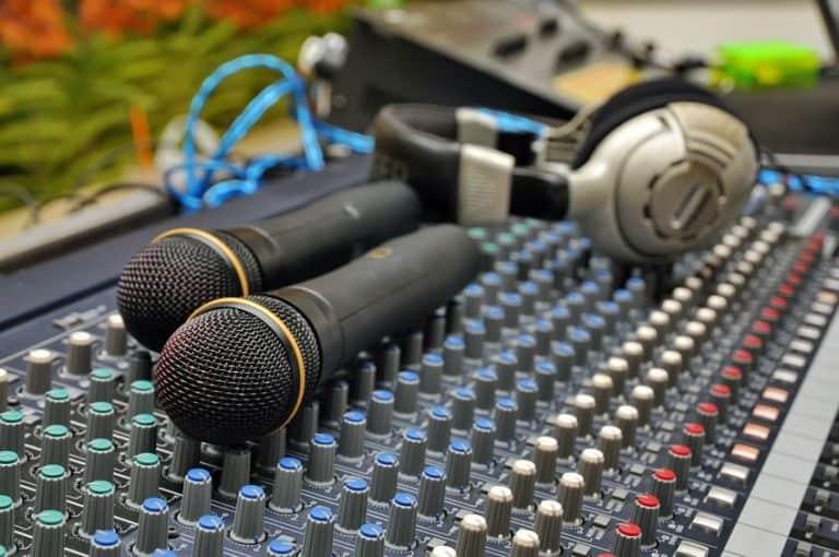 Imagem de dois microfones sobre mesa de som, com fones de ouvido ao lado.