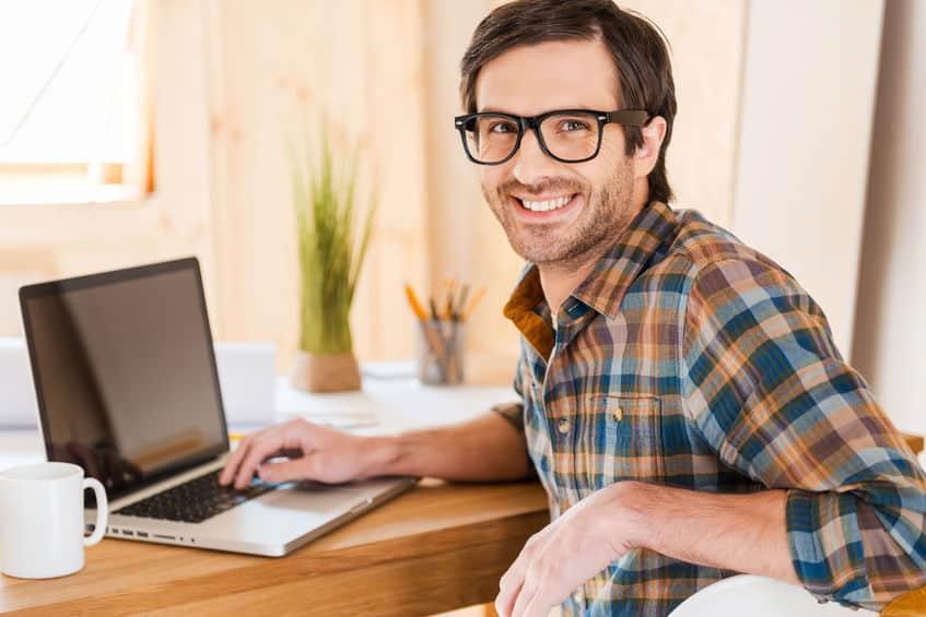 Homem sentado em frente a um notebook, olhando para a câmera