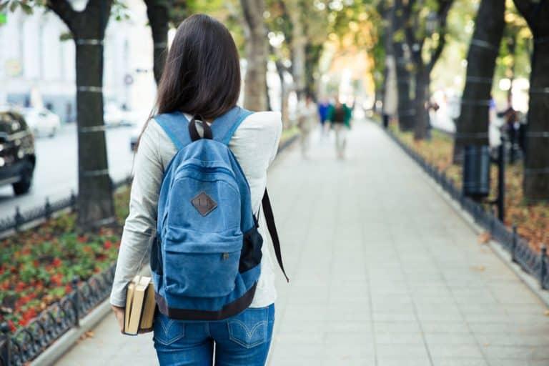 Mulher caminhando com mochila nas costas e livros na mão.