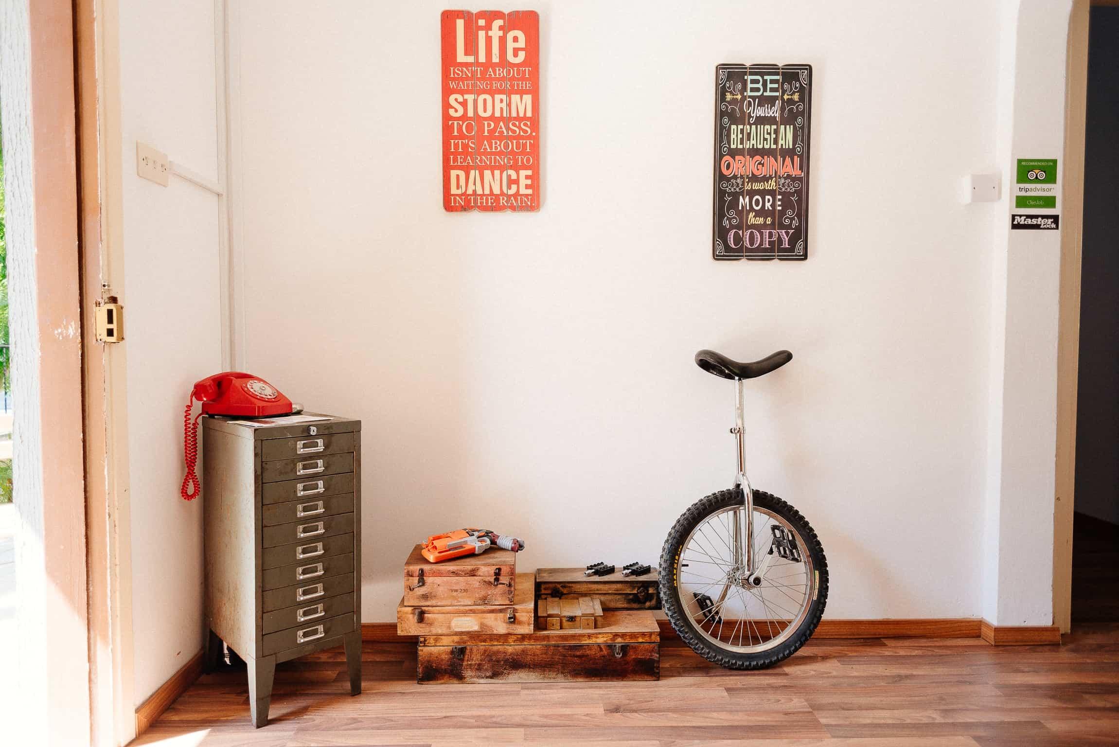Imagem de monociclo encostado em parede de casa.