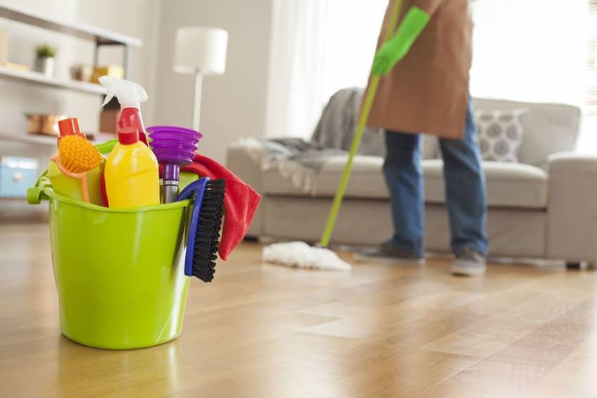 Imagem e pessoa esfregando chão da sala com mop e produtos de limpeza na frente.