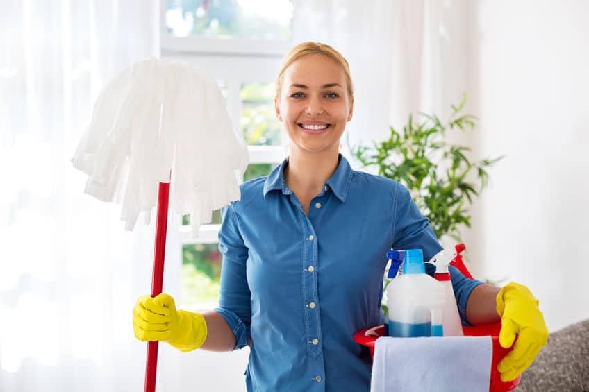 Imagem de mulher segurando mop e produtos de limpeza.
