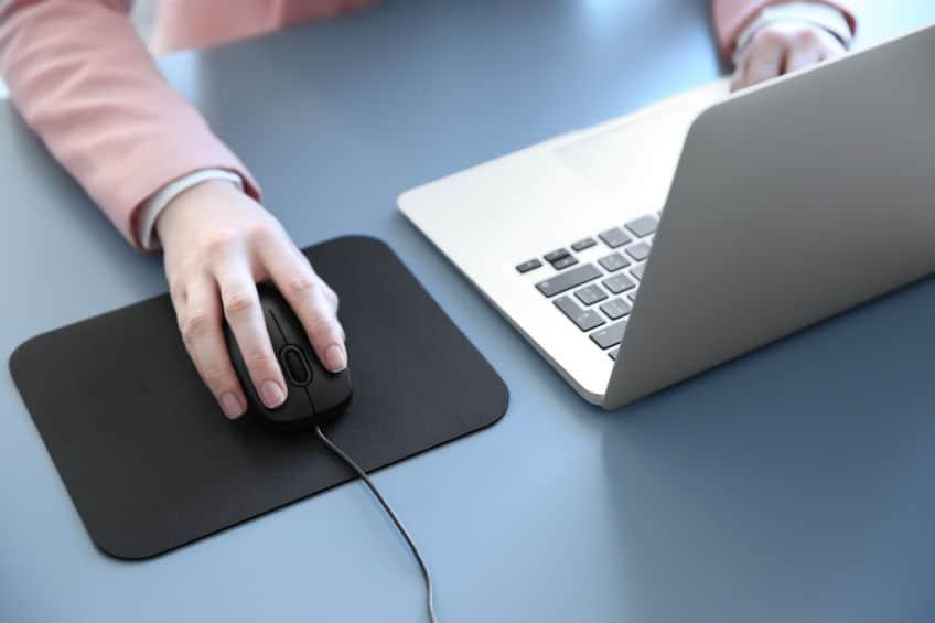 Imagem de pessoa trabalhando em frente a computador segurando mouse.