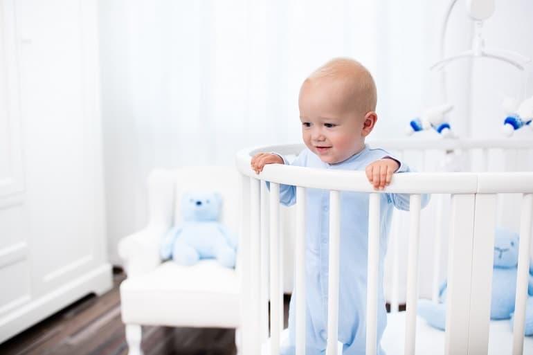 Bebê em pé dentro de berço.