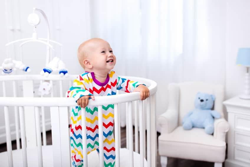 Bebê de pé dentro do cercadinho com móbile