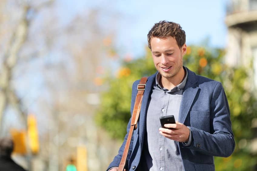 Imagem de homem andando segurando celular.