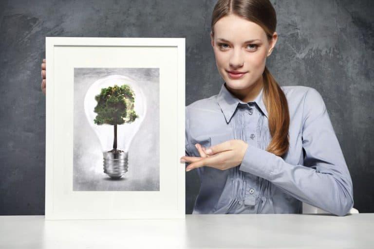 Imagem de mulher segurando quadro com lâmpada.