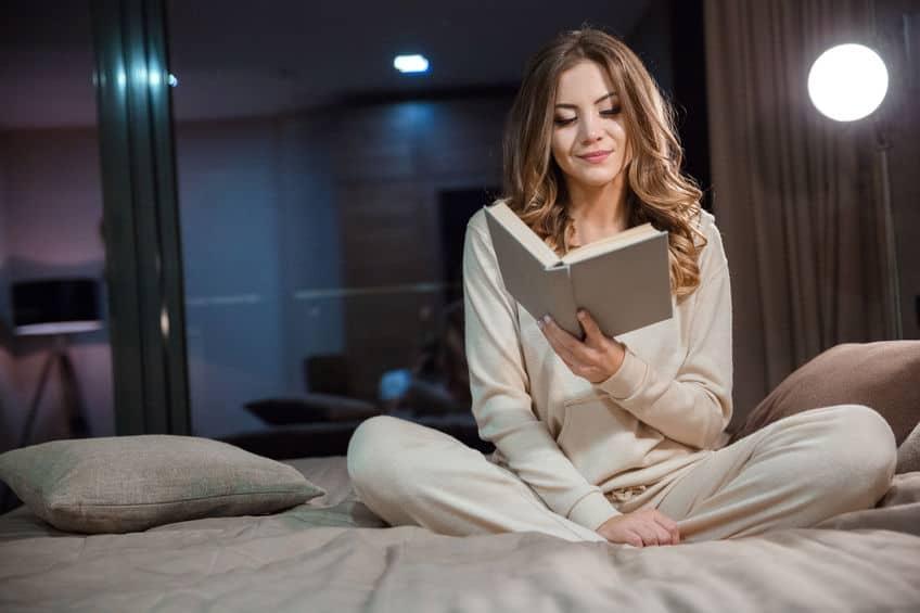 Mulher na cama lendo.