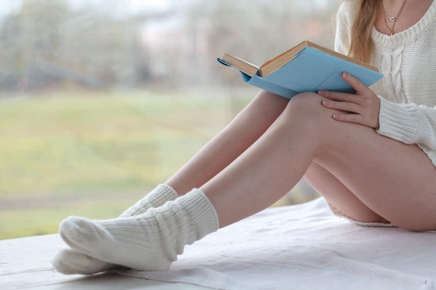 Imagem de mulher lendo livro com capa azul.