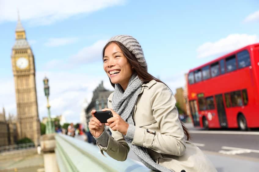 Imagem de mulher tirando foto com celular em Londres.