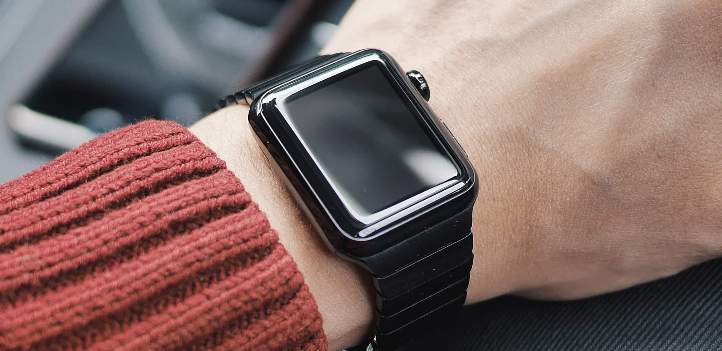 Imagem de homem olhando para relógio e segurando smartphone.