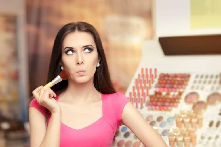 Mulher passando um pincel de maquiagem no rosto
