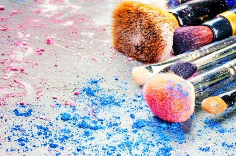 Diversos pinceis de maquiagem com sombras coloridas espalhadas