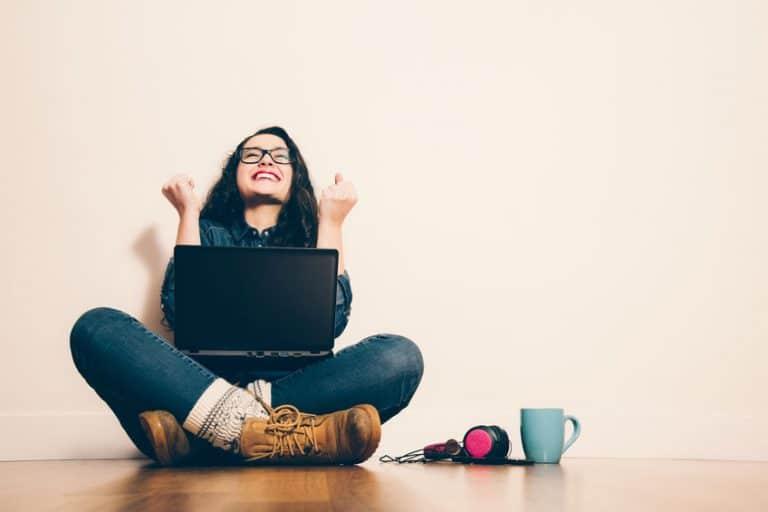 Mulher vibrando com notebook gamer no colo.
