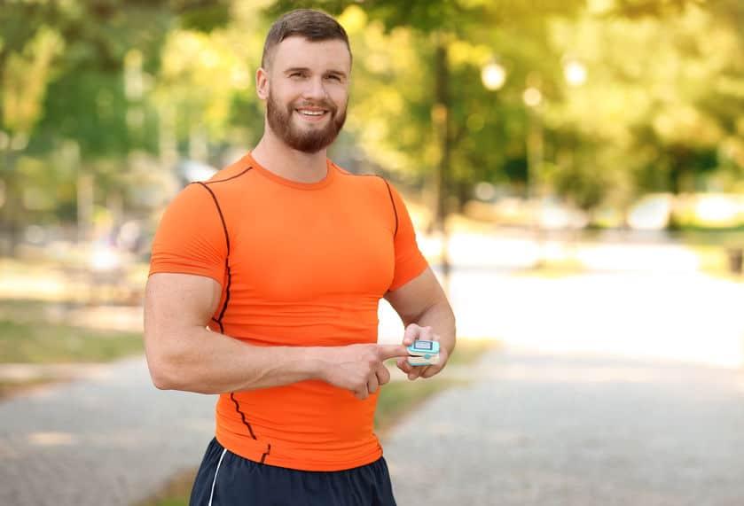Imagem de homem medindo pulso com oximetro.