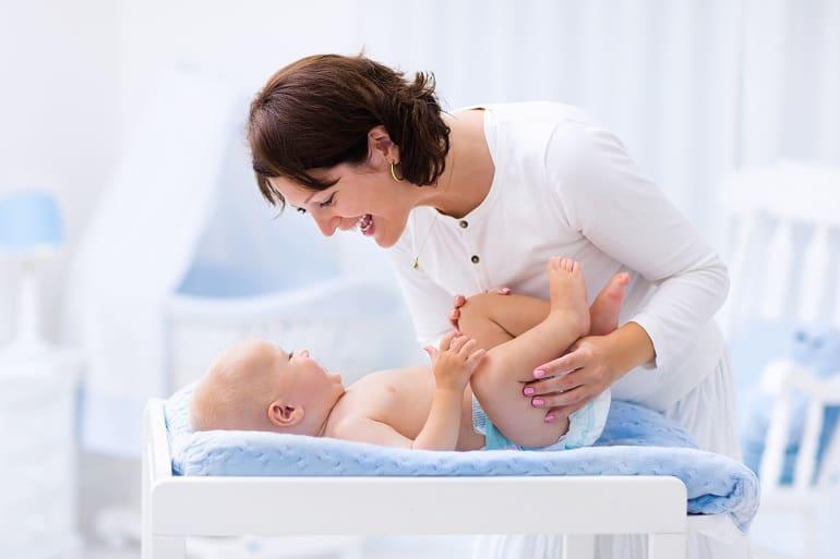 Imagem de mãe trocando fralda de bebê.
