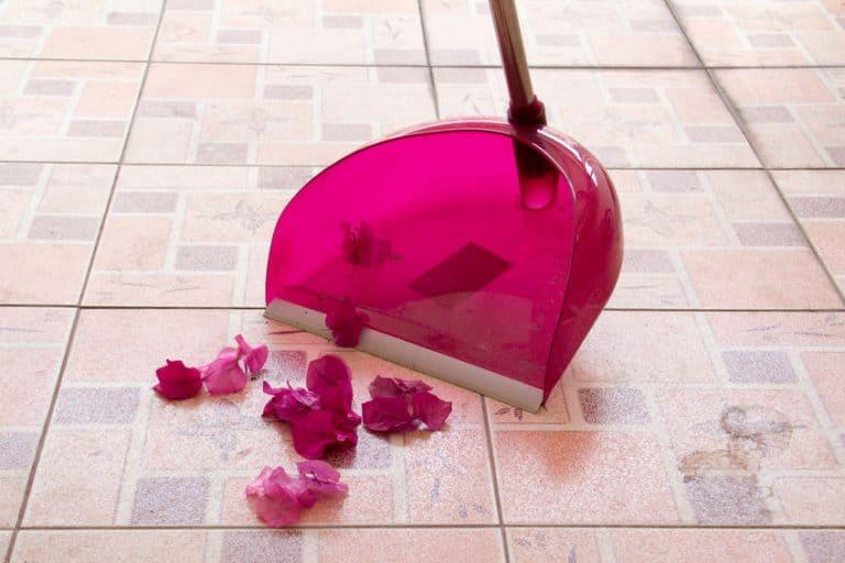 Pá de lixo rosa recolhendo lixo.