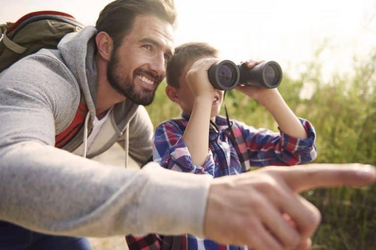 Pai e filho observando com binóculos.