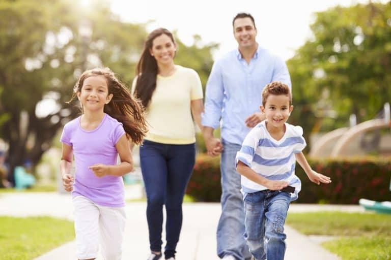 Pais e filhos correndo em parque.