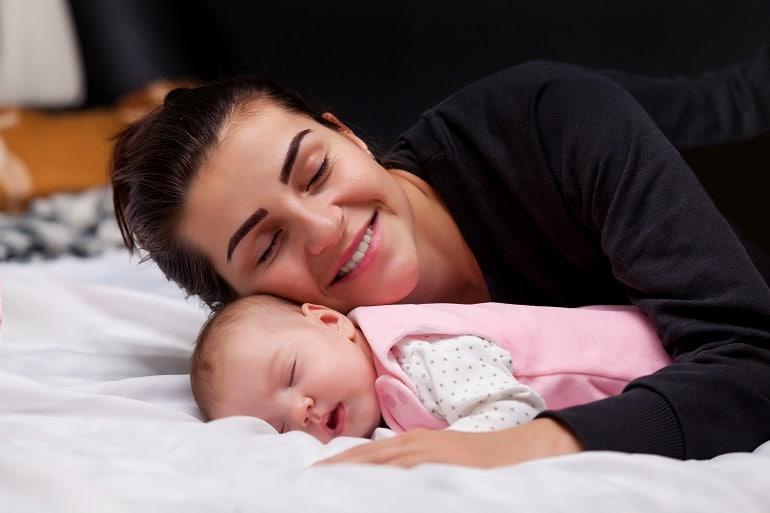 Mãe abraçando bebê que está dormindo.