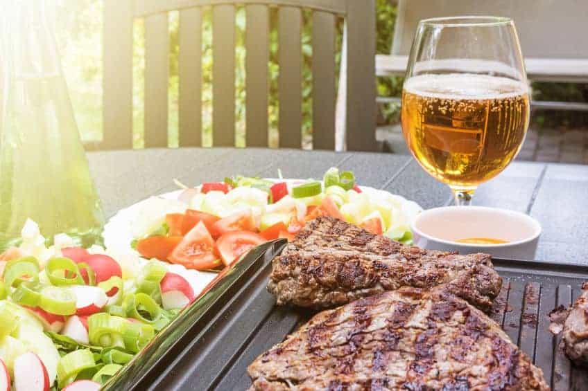 Imagem de churrasco, legumes e cerveja sobre mesa.