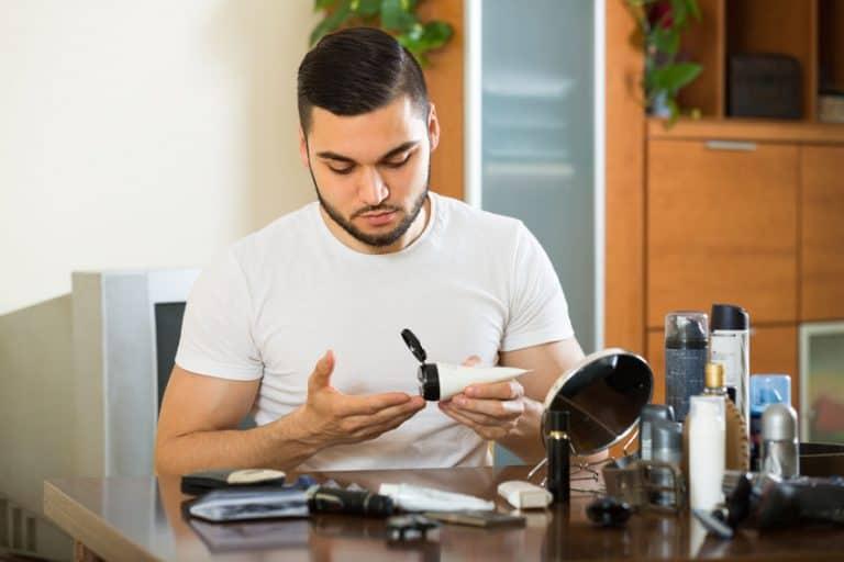 Homem passando produto na barba.