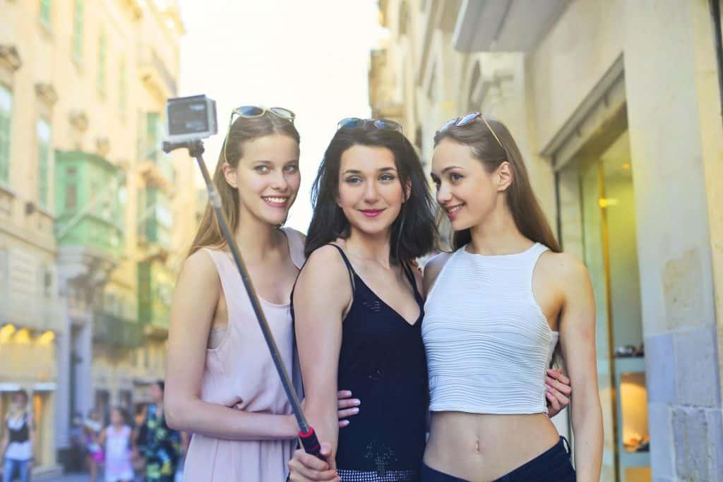 Amigas passeando fazendo selfie.