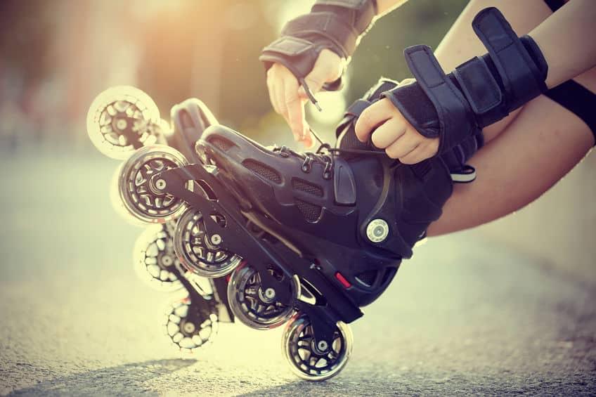 Imagem de pessoa calçando seus patins em linha.