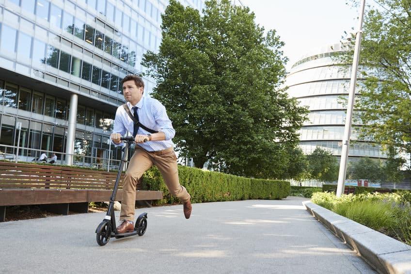 Imagem de homem andando de patinete.