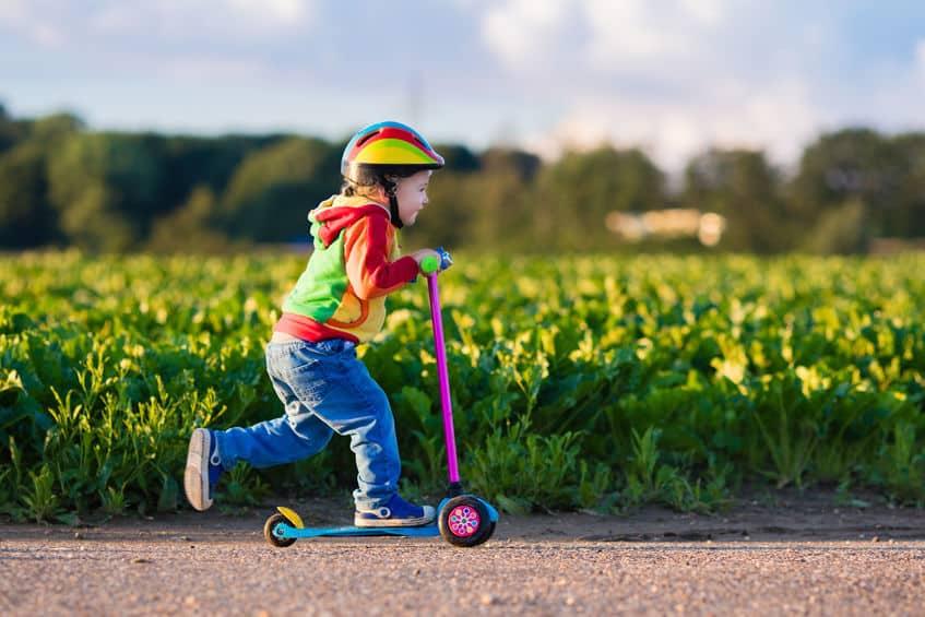 Imagem de menina andando de patinete.