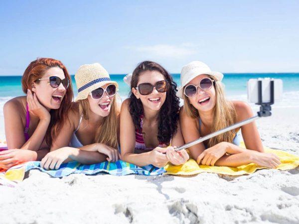 Amigas na praia fazendo selfie.