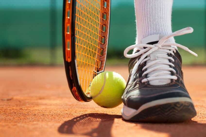 Pé de um jogador de tênis com bola e raquete ao lado.