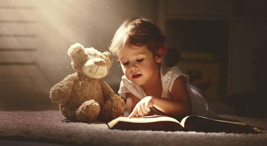 Imagem de menina lendo livro ao lado de ursinho de pelúcia.
