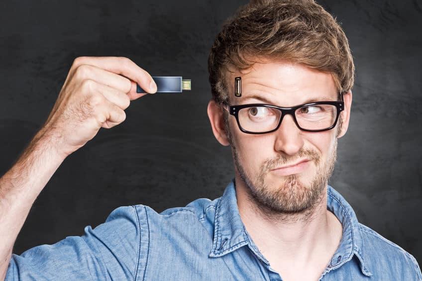 Homem segurando um pen drive como se fosse conectá-lo na cabeça