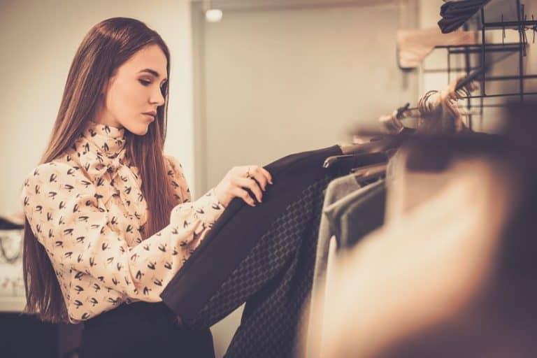 Mulher mexendo em cabides escolhendo roupas.